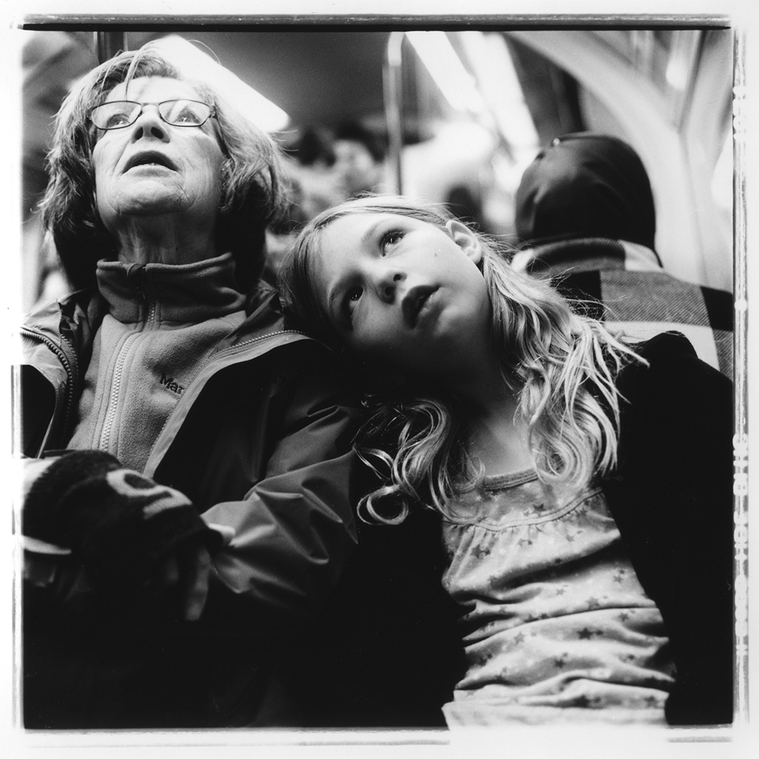 Documentary street portrait of Grandma and Sydney finding the next stop on the London Underground.  Portrait photographed with a Rolleiflex 2.8e on Ilford HP5 120 film.