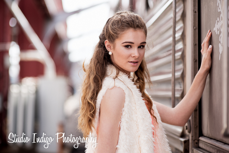 """Medium length portrait of high school student Sarah leaning on train.  I would call this a senior """"fashion"""" style portrait session.  Shot entirely with natural light and post processing with lightroom, photoshop and alienskin software."""